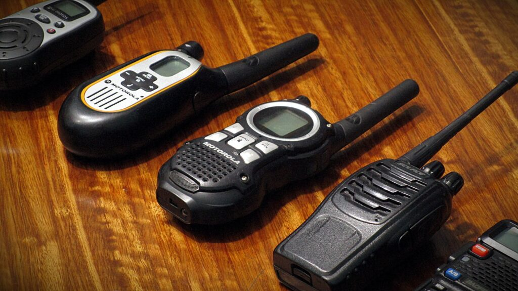 Five different PMR446 Hand Held radios lie on a wooden table. More basic models to the left and more profesional models to the right.