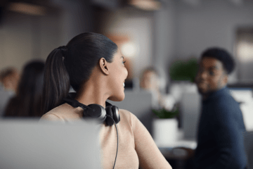 Lady wearing her headset artound her neck leaning back to talk to her colleague.
