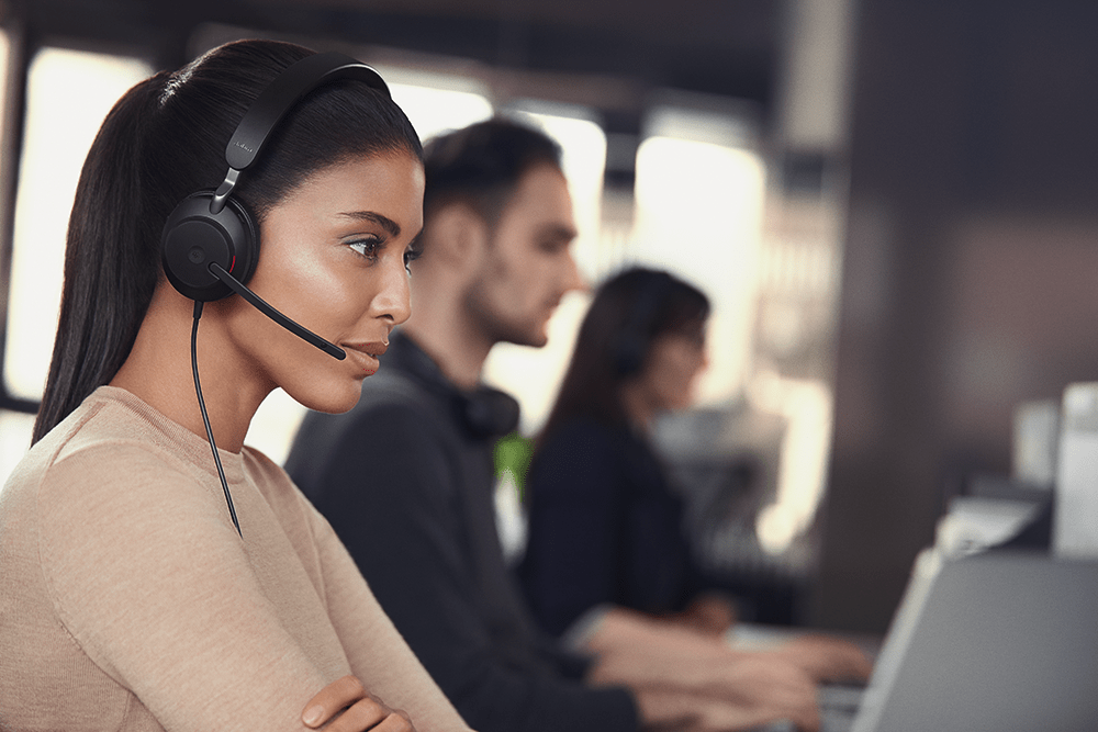 Lady in a busy office wearing a modern wired headset