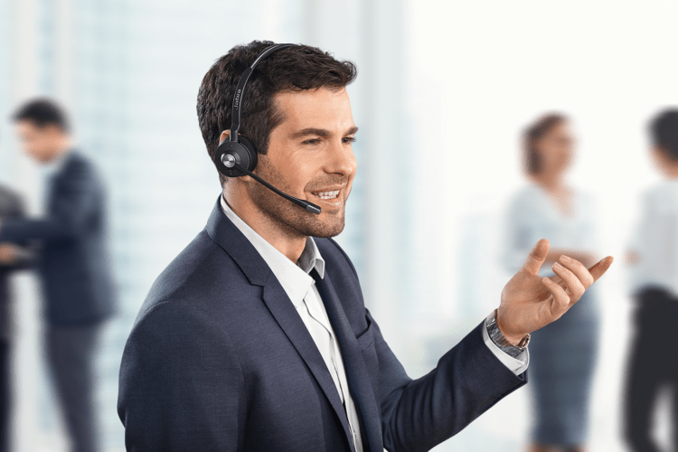 Man wearing a Jabra Engage 75 Headset whilst standing with co-workers int he background